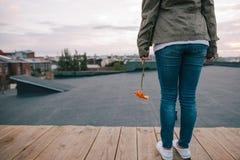Jonge vrouw die terug met oranje bloem blijven Royalty-vrije Stock Afbeeldingen