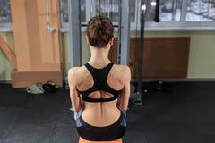 Jonge Vrouw die terug op Machine in de Gymnastiek uitoefenen en Spieren buigen - het Spier Atletische Model van de Bodybuilderges Royalty-vrije Stock Fotografie