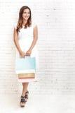 jonge vrouw die terwijl het dragen het winkelen in zakken doet glimlachen Royalty-vrije Stock Foto's