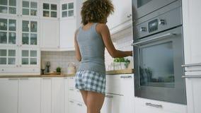 Jonge vrouw die terwijl het koken dansen stock videobeelden