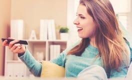 Jonge vrouw die terwijl het letten van op TV in haar huis glimlachen Stock Fotografie