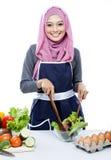 Jonge vrouw die terwijl het maken van salade glimlachen stock foto