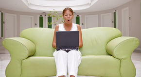 Jonge vrouw die terwijl het werken aan laptop geeuwt royalty-vrije stock afbeelding