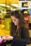 Jonge vrouw die terwijl het winkelen glimlacht stock foto's
