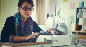Jonge vrouw die terwijl het zitten op haar werkende plaats naaien Stock Afbeeldingen