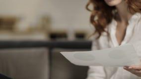 Jonge vrouw die thuis werken Zitting van de close-up de vrouwelijke persoon op bank met laptop stock videobeelden