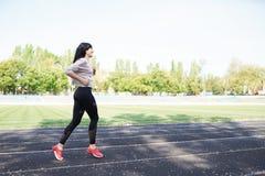 Jonge vrouw die tijdens zonnige ochtend op stadionspoor lopen Het verlies van het gewicht Gezonde Levensstijl Sportief gezond wij royalty-vrije stock afbeelding