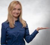 Jonge vrouw die in toevallig blauw overhemd met open hand recht in camera kijken stock afbeeldingen