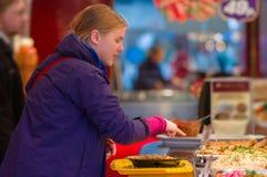 Jonge vrouw die tot schotels in restaurant opdracht geeft Royalty-vrije Stock Foto's