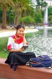 Jonge vrouw die traditionele Andesrok en blouse met de aanpassing van rode halsband dragen, die op bank naast meer aanwezig zijn Royalty-vrije Stock Foto