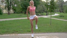 Jonge vrouw die training in park op een bank doen stock video