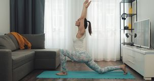 Jonge vrouw die training thuis doen Geschiktheidsmeisje die yogaoefeningen op mat doen Gezonde en sportlevensstijl stock footage