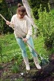 Jonge vrouw die in tuin werken Royalty-vrije Stock Afbeelding