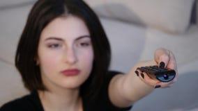 Jonge vrouw die TV-op zitting op vloer thuis letten stock videobeelden