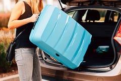 Jonge vrouw die twee blauwe plastic koffers laden aan autoboomstam stock foto's