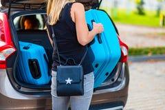 Jonge vrouw die twee blauwe plastic koffers laden aan autoboomstam royalty-vrije stock afbeeldingen