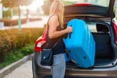 Jonge vrouw die twee blauwe plastic koffers laden aan autoboomstam royalty-vrije stock afbeelding