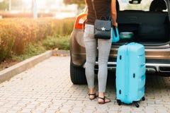 Jonge vrouw die twee blauwe plastic koffers laden aan autoboomstam stock afbeelding
