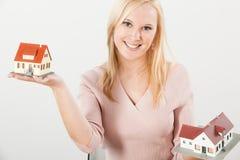 Jonge vrouw die twee huizen met handen in evenwicht brengt Stock Fotografie