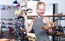 Jonge vrouw die twee paren nieuwe schoenen kiezen Royalty-vrije Stock Afbeelding