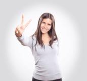 Jonge vrouw die twee vingers tonen stock foto's