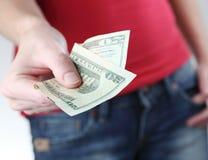 Jonge vrouw die u geld overhandigt Royalty-vrije Stock Afbeeldingen