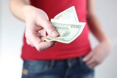 Jonge vrouw die/u geld overhandigt geeft Royalty-vrije Stock Afbeeldingen