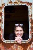 Jonge vrouw die uit het venster van een roestige wagen kijken stock afbeeldingen