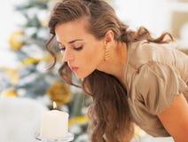 Jonge vrouw die uit kaars voor Kerstmisboom blaast Stock Foto