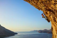 Jonge vrouw die uitdagingsroute beklimmen bij zonsondergang royalty-vrije stock fotografie