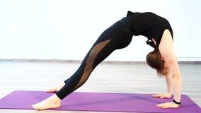 Jonge vrouw die uitrekkende oefening op een mat in een geschiktheidsstudio doen stock footage