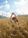Jonge vrouw die van aard en zonlicht op strogebied genieten Royalty-vrije Stock Foto's