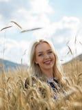Jonge vrouw die van aard en zonlicht op strogebied genieten Royalty-vrije Stock Afbeeldingen