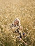 Jonge vrouw die van aard en zonlicht op strogebied genieten Stock Fotografie