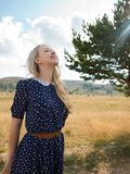 Jonge vrouw die van aard en zonlicht op strogebied genieten Stock Afbeelding