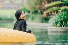 Jonge vrouw die van buizenstelsel genieten bij luie rivierpool stock foto's