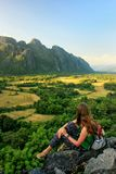 Jonge vrouw die van de mening van landbouwbedrijfgebieden genieten in Vang Vieng, Laos stock fotografie