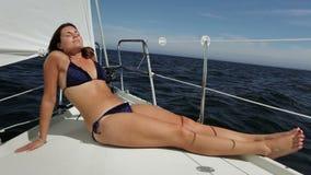 Jonge vrouw die van de zon en van het overzees genieten die een zonnige dag in de archipel van Stockholm, Zweden varen stock videobeelden