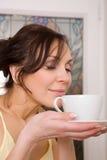Jonge vrouw die van een kop thee geniet Royalty-vrije Stock Foto's