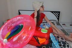 Jonge vrouw die van een zitting van de wereldreis met haar wapensresti dromen Stock Fotografie