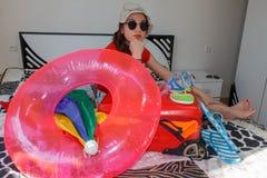 Jonge vrouw die van een zitting van de wereldreis met haar wapensresti dromen Stock Foto