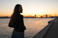 Jonge vrouw die van een zonsonderganggang langs de rivier Daugava met een mening over duidelijke blauwe hemel genieten royalty-vrije stock afbeelding