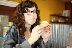 Jonge vrouw die van gebakje genieten Royalty-vrije Stock Foto's
