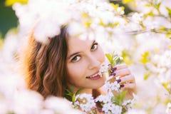 Jonge vrouw die van geur van bloeiende boom genieten Stock Afbeeldingen