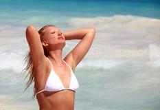 Jonge vrouw die van het strand op zonnige dag geniet Stock Foto's