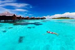 Jonge vrouw die van hut in tropische lagune zwemmen Royalty-vrije Stock Fotografie