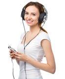 Jonge vrouw die van muziek geniet die hoofdtelefoons met behulp van Royalty-vrije Stock Afbeelding