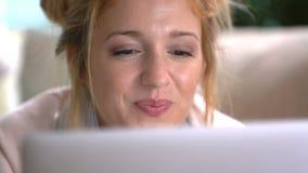 Jonge vrouw die van online mededeling die over laag genieten liggen Dolly schot stock video