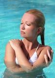 Jonge vrouw die van zon in zwembad geniet Stock Afbeelding