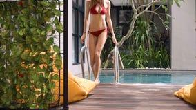 Jonge vrouw die van zwembad opstappen stock footage